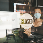 Storefront with Quarantine Sign and Worker with Mask