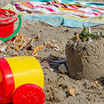 Beach with sand toys with cigarettes in them